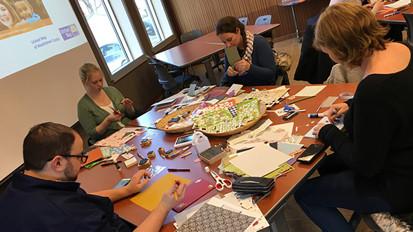Five Academic Innovation staff members cutting construction paper while seated at table covered in craft supplies