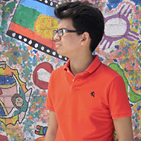 Young man looking in the distance standing in front of a wall of graffiti