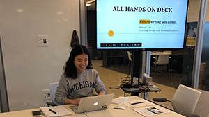 "Yuanru Tan seated at the end of a large conference room tab with a monitor behind her reading ""All Hands on Deck, Alt Text Writing Jam @DEIL"""